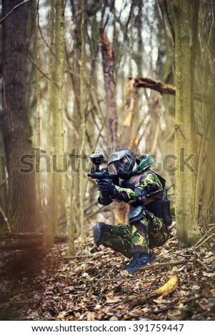 Paintball player in protective uniform and mask aiming gun in the forrest cover - stock photo