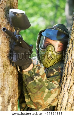 paintball sport player in protective uniform and mask aiming gun to enemy from shelter outdoors - stock photo