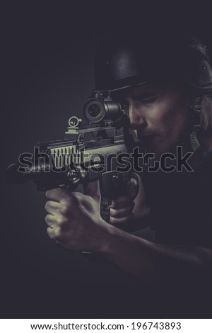 paintball sport player wearing protective helmet aiming pistol ,black armor and machine gun - stock photo