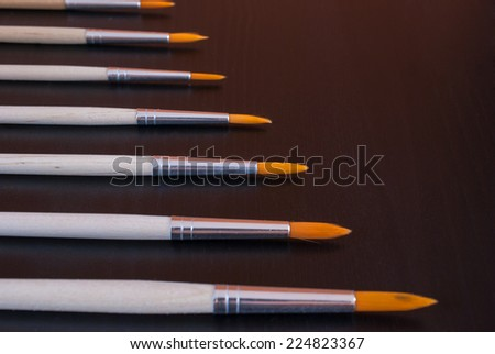 Paintbrush set, different size round brushes with easy-to-clean polyester bristles, on wooden background - stock photo
