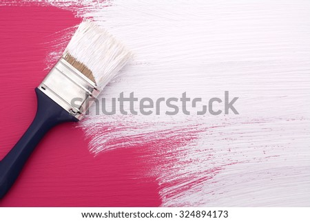 Paintbrush with white paint painting over deep pink color on a pine board - stock photo