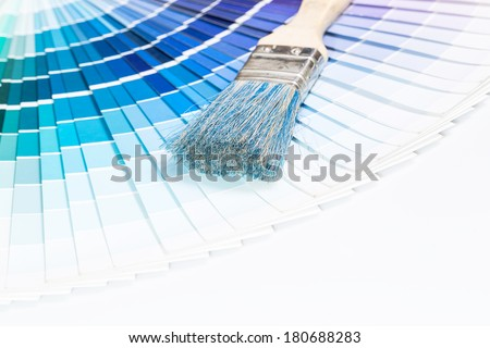 Paintbrushes and blue color samples over white background. - stock photo