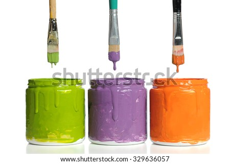 Paintbrushes dripping paint into containers with secondary colors isolated over white background - stock photo