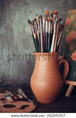 Paintbrushes in a jug from potters clay, palette, paint tubes and Painting in artist studio. - stock photo