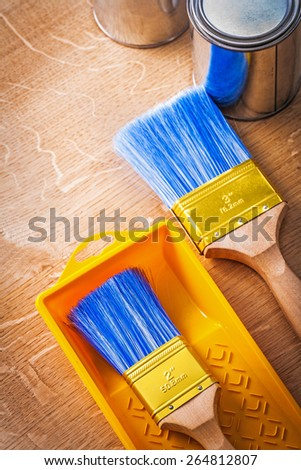 paintbrushes with metalic paint cans and tray construction concept  - stock photo