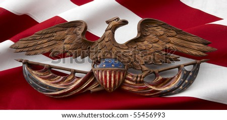 Painted, carved, wooden American Eagle shot on red and white stripes of the flag - stock photo