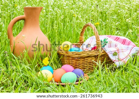 Painted Easter eggs and toy chicks on a background clay pitcher, a wicker basket under the checkered napkin and green grass - stock photo