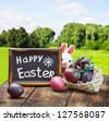 Painted Easter eggs in a basket on the table with a congratulatory text - stock photo