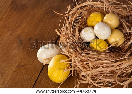 Painted Easter eggs in nest of twigs and straw in rustic setting - stock photo
