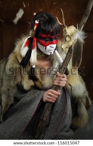 Painted face, native american woman with war mask. Cracked paint. Young shaman girl with deer skull staff part of large series of painted tribal portraits - stock photo