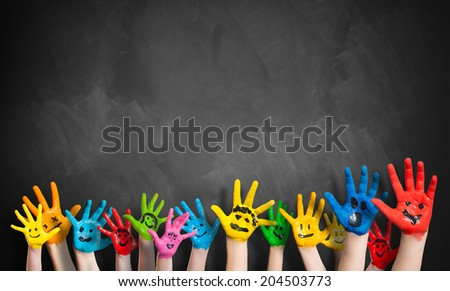 painted hands in front of a blackboard - stock photo