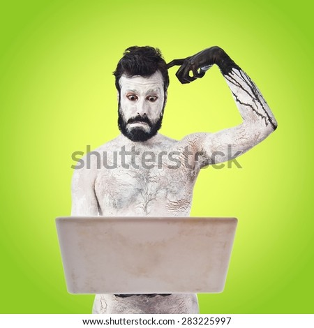 Painted man with laptop over colorful background - stock photo