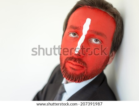 Painted man with red face and white line on nose - stock photo