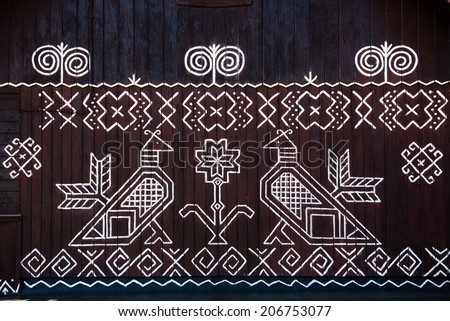 painted pattern on side of log house in Cicmany, UNESCO World Heritage Site, Slovakia - stock photo