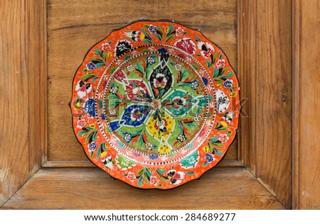 painted plates on the background of wooden furniture - stock photo