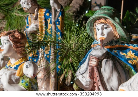 Painted pottery statue of a man playing the characteristic zampogna in the ceramic nativity scene of an artisan in Caltagirone - stock photo
