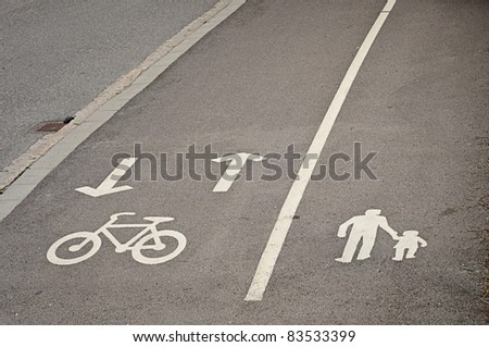 Painted signs on asphalt for pedestrian and bicycle dedicated lanes - stock photo