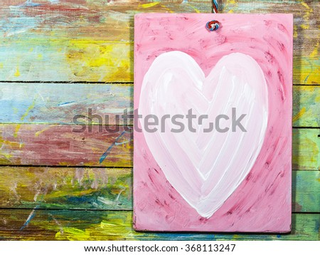 Painted white heart hang on retro colorful  painted wooden background,valentine background with copy space - stock photo