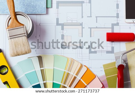 Painter and decorator work table with house project, color swatches, painting roller, brush and tools, top view - stock photo