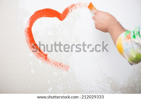 Painter drawing very nice heart on the white linen - stock photo
