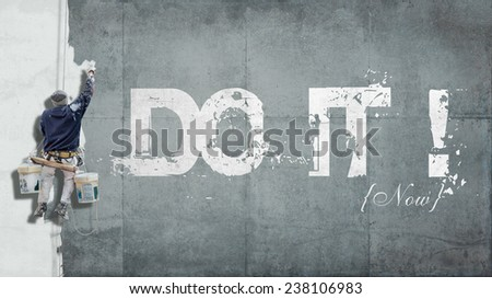 Painter hanging from harness painting a wall with the words do it now - stock photo
