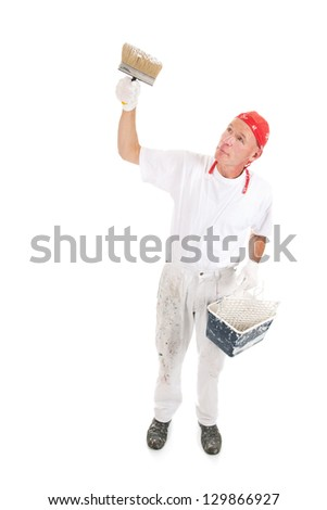 Painter in studio working with big block brush for ceiling - stock photo