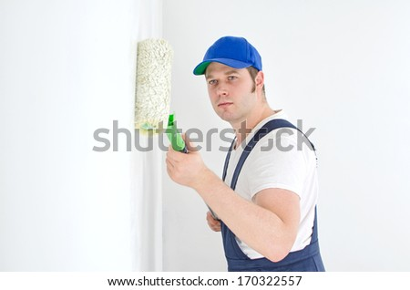 Painter in uniform paints the wall. Space for your text. - stock photo