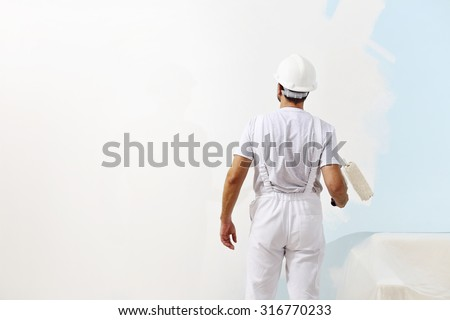 painter man at work with a paint roller, wall painting concept - stock photo