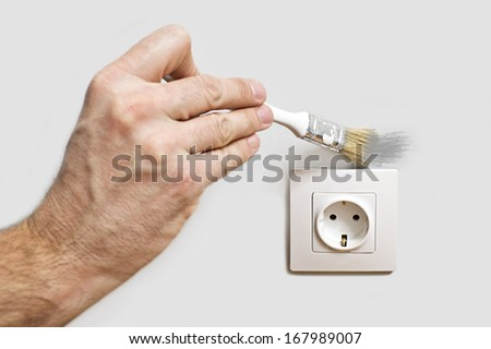 Painter painting wall around of electric plug outlet - stock photo