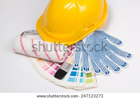 painter's tools - brushes, work gloves, yellow helmet and colorful palette over white background - stock photo