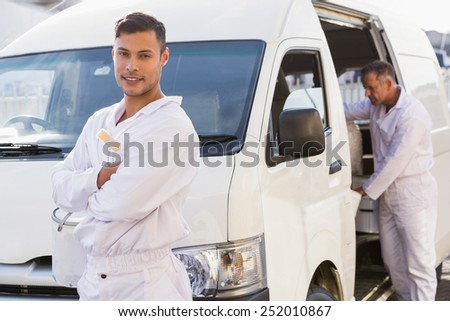 Painter smiling leaning against his van outside the warehouse - stock photo