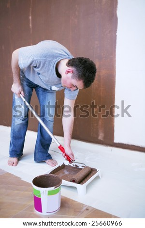 Painter using a paint roller - stock photo