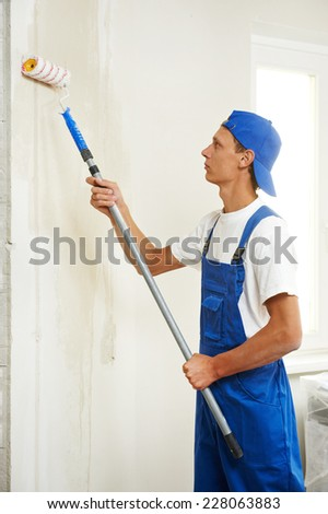 painter with paint roller making wall prime coating  at home repair renovation work - stock photo