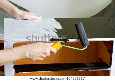 painter with paint roller painting a wooden commode - stock photo