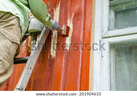 Painter worker man on ladder paint wooden rural house wall with brush paintbrush near window.  - stock photo