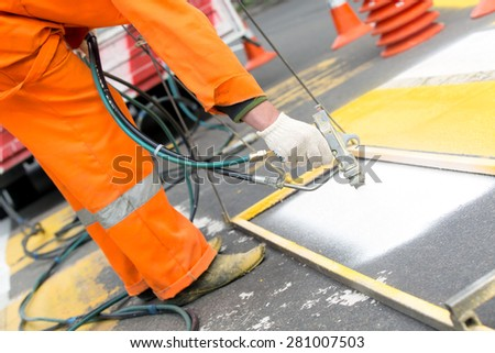 Painter worker traffic sign on asphalt pavement marking with spray gun - stock photo