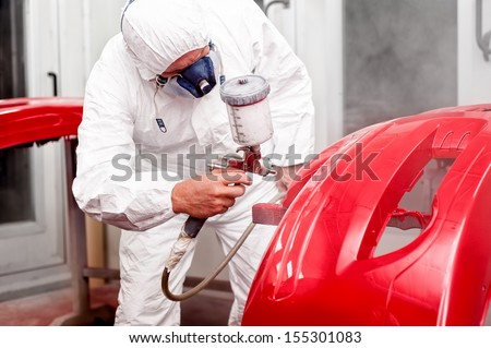 Painter working and painting a red car in paint garage - stock photo