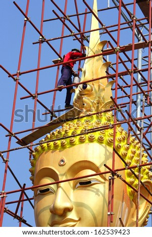 Painters are painting  big  golden Buddha statue under construction  in Thai  temple - stock photo