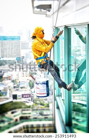 Painters high building condo outdoors sprinkle with rope safe sure in bangkok thailand. - stock photo