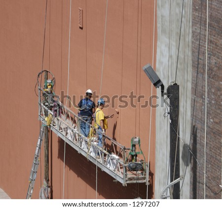 Painters on the side of a building with copy space for text - stock photo