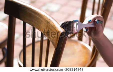 Painting a chair with a brush - stock photo