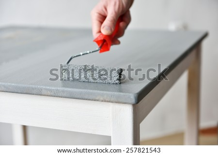 Painting a table using paint roller - stock photo