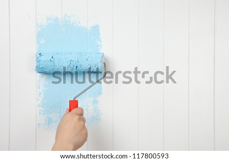 Painting a wall in blue - stock photo