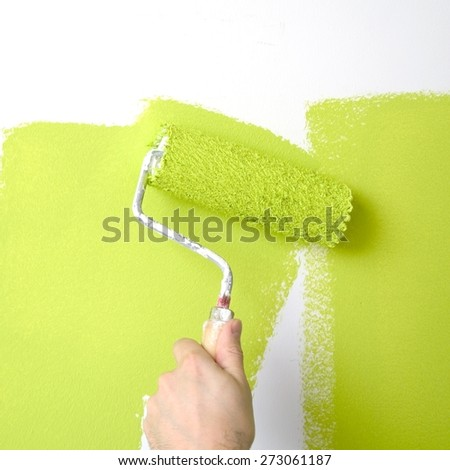 painting a wall with a roll into salad color - stock photo