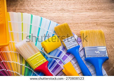 painting composition three paint brushes and roller on color palette wooden board construction concept  - stock photo