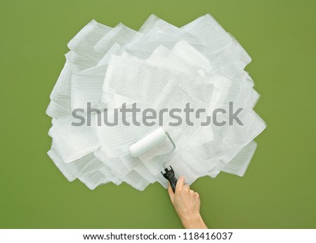 Painting green wall in white color with paint roller. Acrylic paint texture. - stock photo