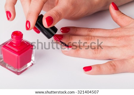 Painting polish on fingers with red nails - stock photo