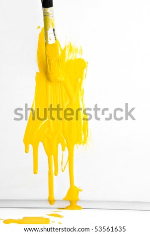Painting the wall with yellow paint and old used brush - stock photo