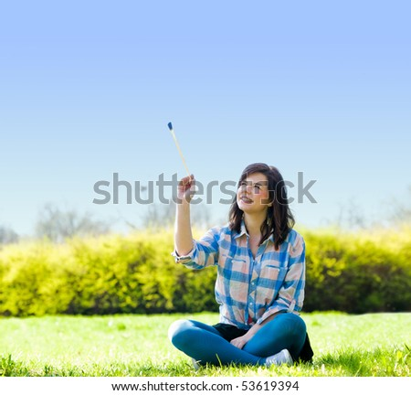 Painting the world. Smiling girl on grass with a paintbrush - stock photo
