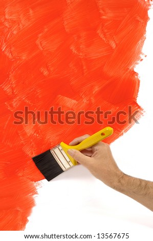 Painting wall : man holding a paintbrush with a partly finished blank red and white painted wall.  Space for copy. - stock photo